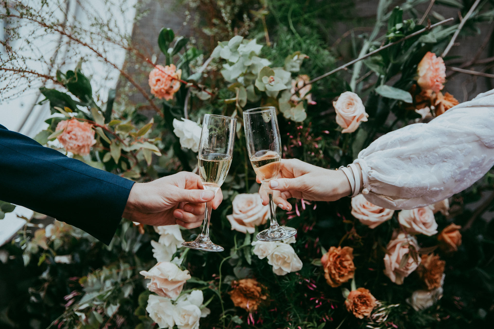 Kristine and Justin toasting with champagne on their wedding day at the Maritime Hotel in NYC with custom Cynthia Rowley wedding dress and roses