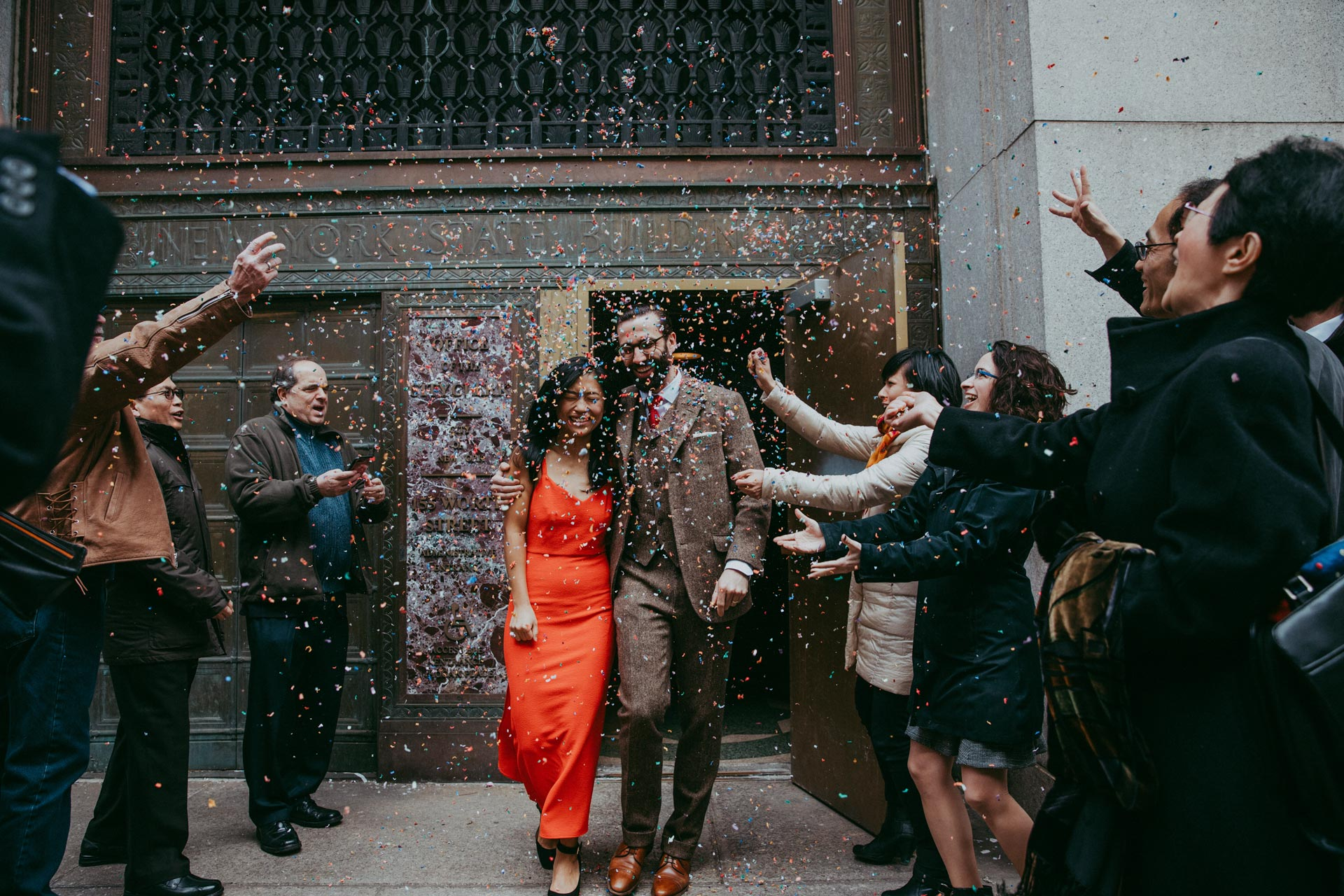Linda and Ben exit Manhattan city hall marriage bureau with red dress and confetti toss in NYC