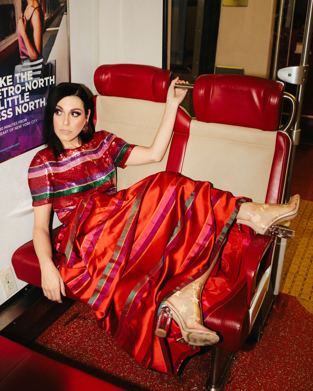 Portrait of actress Natalie Walker wearing a red vintage dress on Metro-North train in Grand Central in NYC