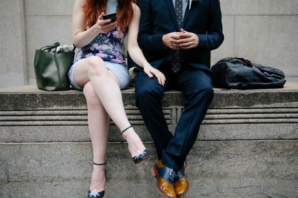 A couple photographed from the neck down with cell phone and stylish shoes after their city hall wedding ceremony in New York, NY