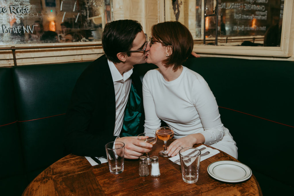 Chelsea Fagan of The Financial Diet kissing her husband after their city hall elopement at Lucky Strike restaurant in New York, NY