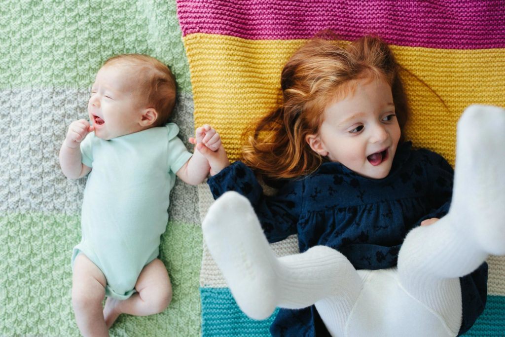 Sisters holding hands on knit blankets at home at family session in New York, NY