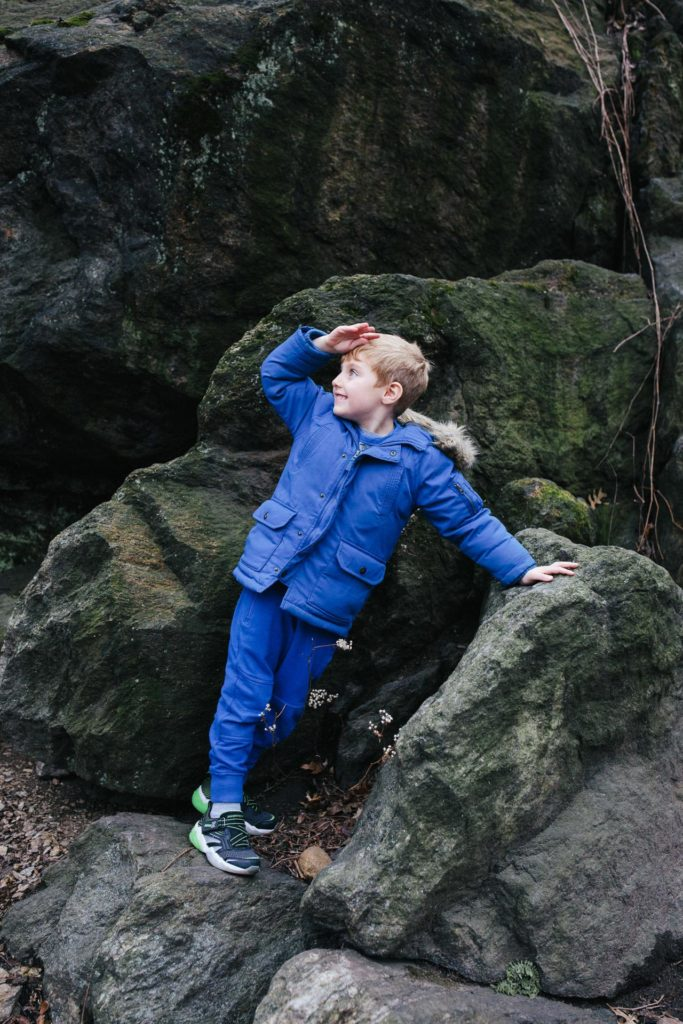 Boy wearing a winter coat playing in the rocks in Central Park, NYC