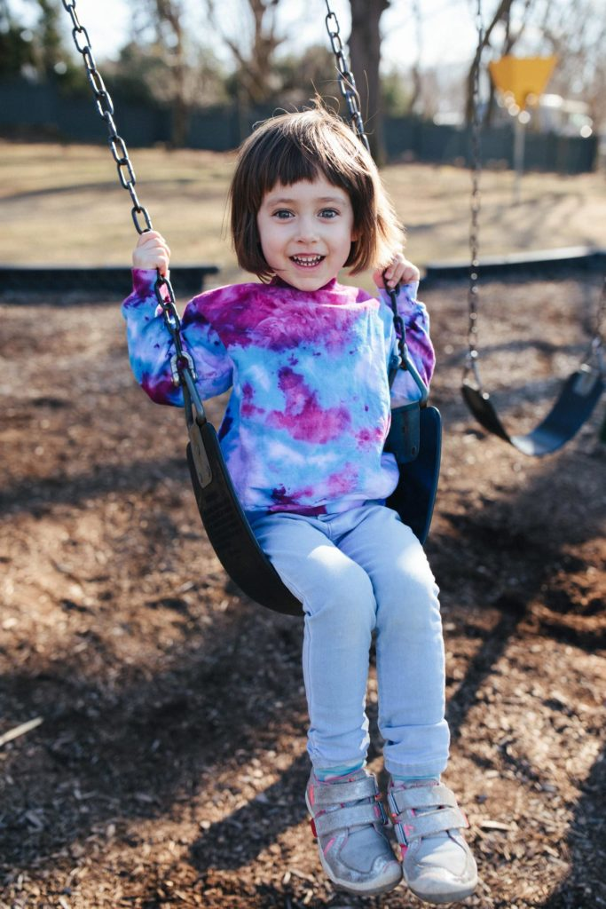 Girl wears tie dyed sweatshirt on a swing at a playground in Irvington, NY