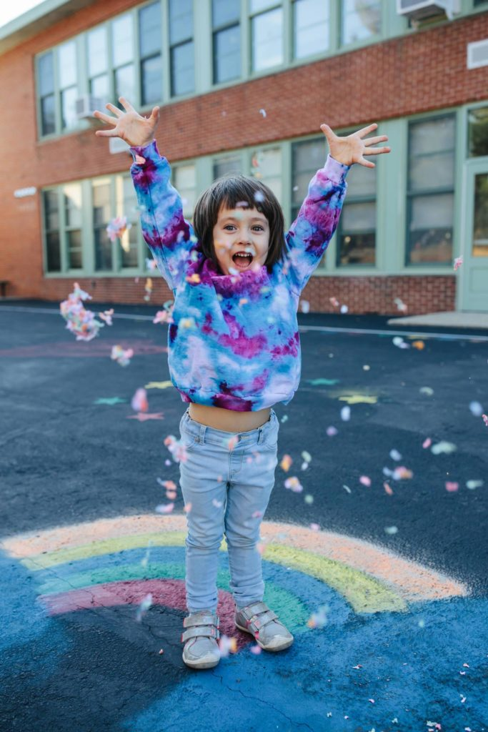 Girl throwing confetti wearing a tie dyed sweatshirt on a playground in Irvington, NY