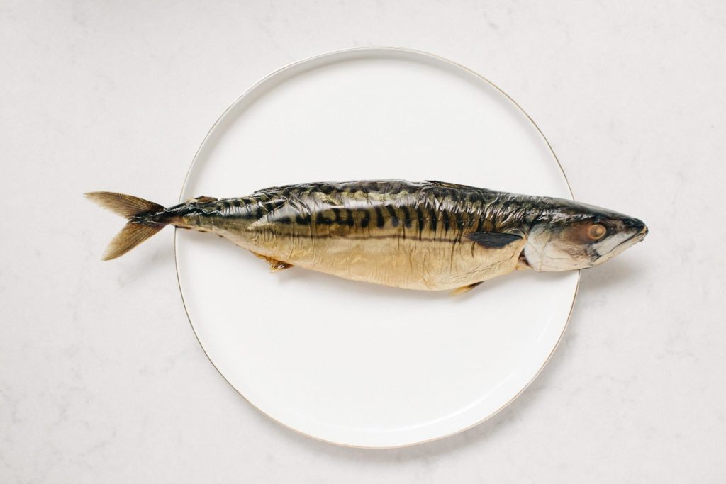 A whole fish on a white dinner plate and marble countertop in Bethesda, PA