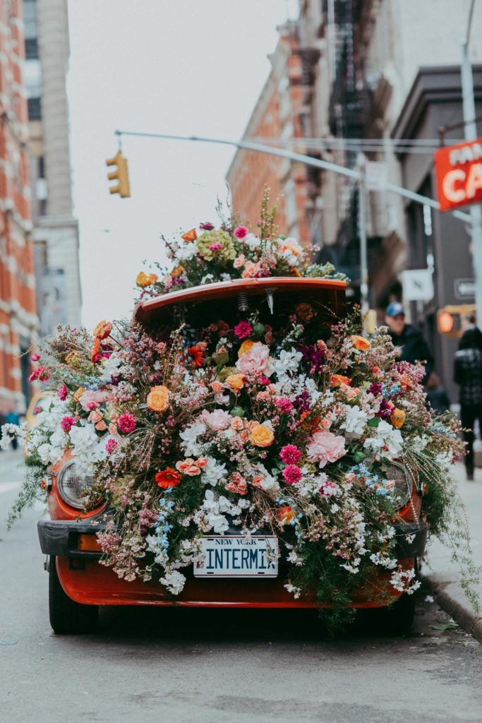 A red car with a trunk full of flowers during a floral installation in SoHo NYC