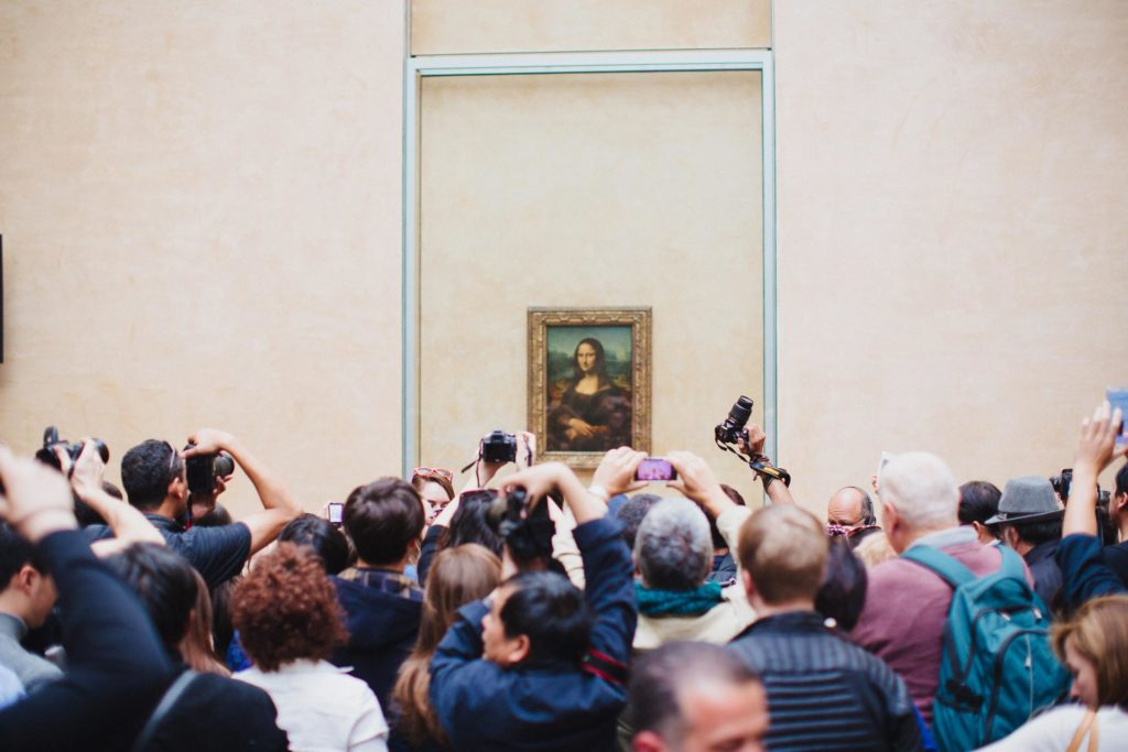 Tourists looking at the Mona Lisa in the Louvre in Paris France