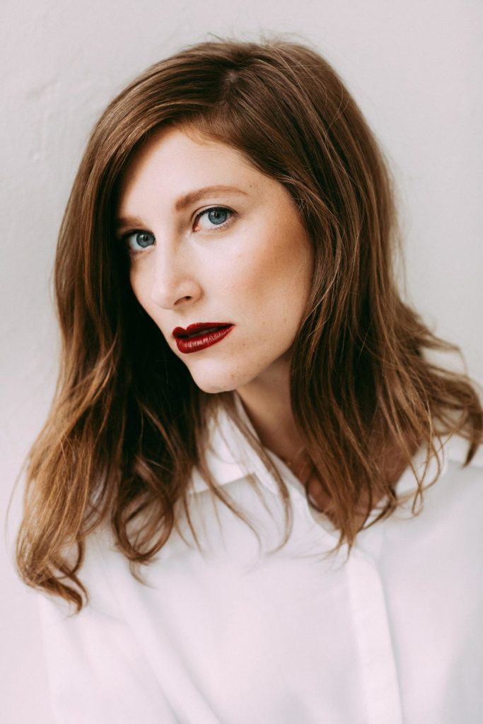 Portrait of Liz wearing a white button-down shirt and deep red lips in New York, NY