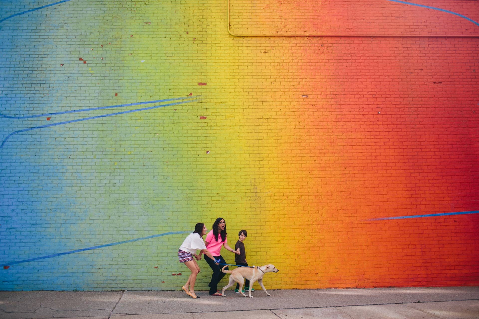 The Leslie family walking their dog in front of a rainbow wall in Brooklyn, New York