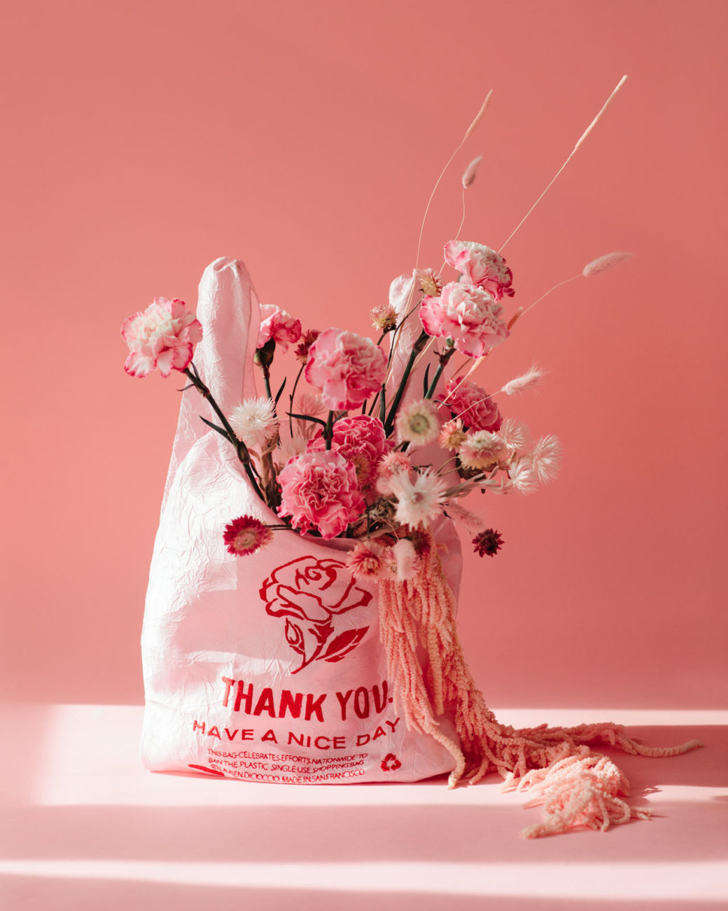 Thank you NYC tote shopping bag with floral installation and dried flowers on a pink background in Queens New York
