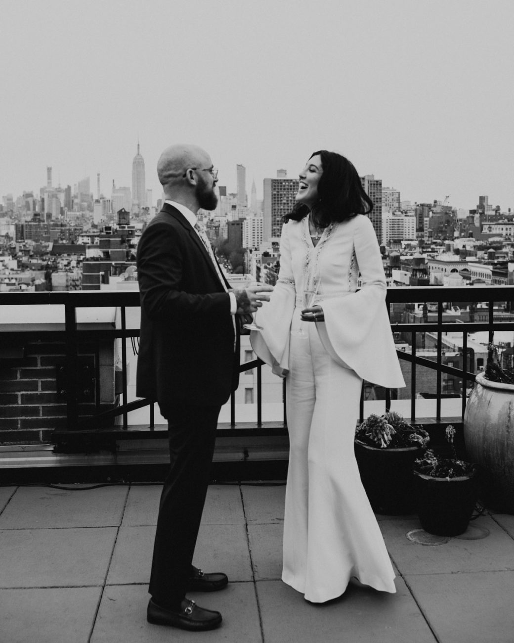 Rata and Ken on the rooftop with NYC skyline in the background after their city hall wedding